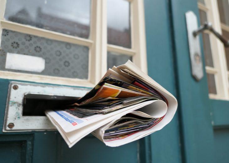 Junk mail stuck in the slot of a door